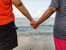 Am Strand gibt es das Liebhaberhändchenhalten, zum Meer unten zu gehen Seashells gestalten auf Sandhintergrund lizenzfreies stockfoto