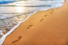 Strand, golf en voetafdrukken in zonsondergangtijd royalty-vrije stock afbeelding