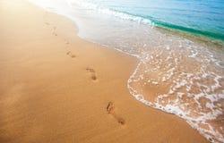 Strand, golf en voetafdrukken in zonsondergangtijd stock foto