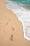 Strand, golf en voetstappen stock afbeeldingen