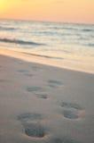 Strand, golf en voetstappen stock afbeelding