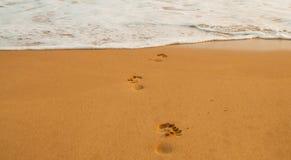 Strand, golf en voetstappen stock fotografie