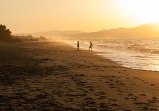 Strand, golf en voetstappen in zonsondergangtijd stock foto