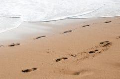 Strand, golven en voetstappen in zonsondergangtijd stock fotografie