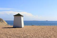 Strand-Hütte, die das blaue Meer gegenüberstellt Stockbilder