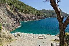 Strand in het overzees dichtbij Cinque Terre in Ligurië De rotsen van de bergen werpen zich in het blauwe overzees stock fotografie