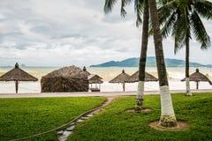 Strand i dåligt väder Tomhet, höga vågor och slags solskydd som göras av naturliga material Arkivfoton