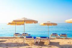 Strand i Lloret de Mar, Spanien Paraplyer och deckchairs på den sandiga stranden royaltyfria bilder