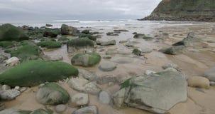 Strand im Cantabric-Meer mit Felsen und im feinen Sand mit Wellen im Hintergrund stock video