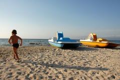 Strand, Junge und pedalos Lizenzfreie Stockfotografie