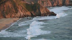 Strand, klippen en golven bij zonsondergang stock video