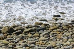 Strand-Kopfsteine und Gezeiten-Schaum Stockfoto