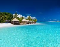 Strand-Landhäuser auf kleiner Tropeninsel Stockfotografie