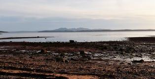 Strand med avlägsna berg på skymning Arkivfoto