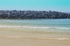 Strand med blått vatten och stora stenar arkivbild