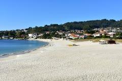 Strand med folk som solbadar och går Ljus sand, träd och blått hav solig dag Pontevedra Spanien, 7 Oktober 2018 arkivfoto