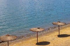 Strand med paraplyer från en ranka Kvalitet och komfort av vilar på vattnet Skydd från solljus Vila på stranden och ponen arkivfoto
