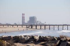 Strand med pir och kraftverk och brygga Royaltyfri Fotografi