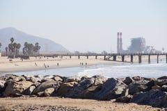 Strand med pir och kraftverket i bakgrund Arkivbild