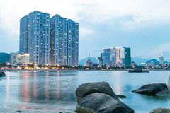 Strand med skyskrapan i skymning med reflexioner i havet royaltyfri fotografi