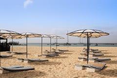 Strand med solparaplyer och sängar royaltyfri bild