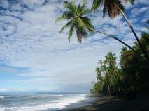 Strand met bewolkte hemel stock foto's