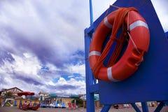 Strand met bewolkte hemel en reddingsdoughnut in de voorgrond, Stock Foto