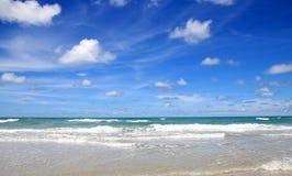 Strand met blauwe hemel en wolken Stock Afbeeldingen