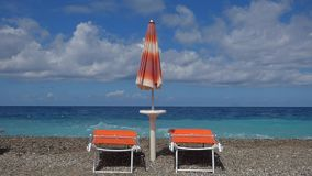 Strand met deckchairs en zonnescherm stock video
