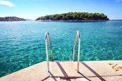 Strand met duidelijk zeewater en eiland royalty-vrije stock afbeelding
