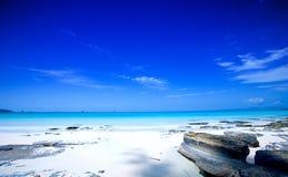 Strand met duidelijke blauwe hemelen en blauwe wateren Stock Foto's