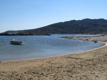 Strand met een boot bij een eiland stock afbeeldingen