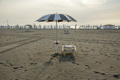 Strand met gesloten paraplu's, klaar zonlanterfanter en geopende paraplu, romantische scène, vroege ochtend in Sottomarina, Itali Royalty-vrije Stock Foto's