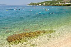 Strand met glasheldere overzees en mensen in Tucepi, Kroatië Stock Foto