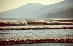 Strand met golven bij zonsondergang Stock Foto