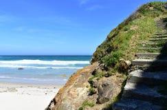 Strand met klip, wit zand, golven en treden Blauwe hemel, zonnige dag, Lugo, Spanje royalty-vrije stock afbeelding