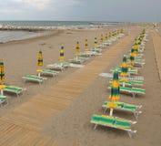 Strand met paraplu's en deckchairs van badmeester het letten op Stock Foto's