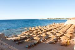 Strand met parasoles en een Rode Overzees met corales stock foto
