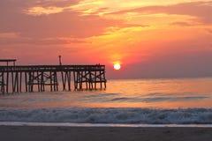 Strand met pijler bij zonsopgang Stock Afbeelding