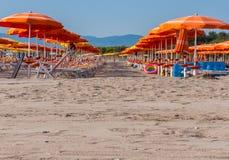 Strand met rijen van oranje paraplu's Stock Afbeelding