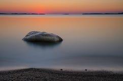 Strand met rots bij zonsopgang stock afbeelding