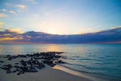 Strand met rotsen bij zonsondergang royalty-vrije stock fotografie