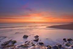 Strand met rotsen bij zonsondergang in Zeeland, Nederland royalty-vrije stock fotografie