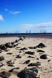 Strand met rotsen die in water leiden Stock Foto's