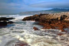 Strand met rotsen, golvenstroom en mist stock fotografie