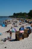 Strand met sommige mensen en ligstoelen met een kap Stock Afbeelding