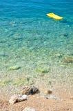 Strand met stenen en geel luchtbed Stock Foto