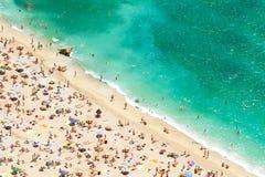 Strand met toeristen, sunbeds en paraplu's stock afbeeldingen