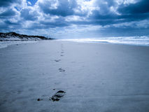 Strand met voetafdrukken die in oneindig leiden stock fotografie