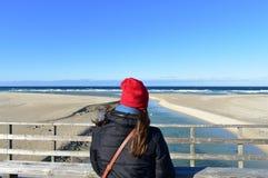 Strand met vrouw die op een houten leuning rusten en de mening bekijken De winterkleren en rode hoed Zonnige dag, blauwe overzees stock afbeeldingen